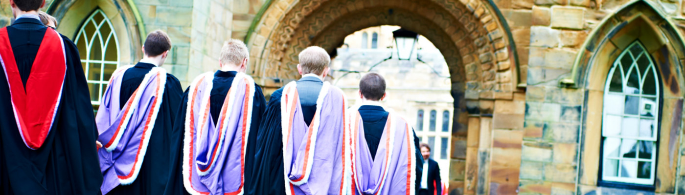 Five graduates walking in a line wearing their gowns, walking towards an arch with their backs towards the camera